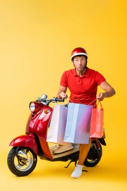 Shocked delivery man in helmet sitting on scooter and holding shopping bags on yellow stock vector