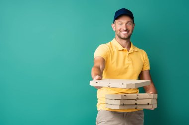 Pleased delivery man with outstretched hand holding pizza boxes on blue stock vector