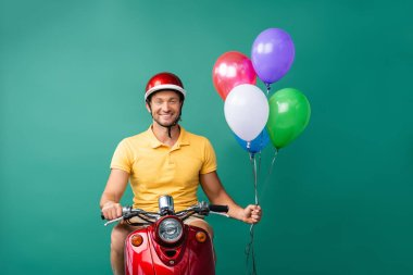 Smiling delivery man in helmet riding red scooter while holding balloons on blue stock vector