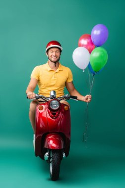 Happy delivery man in helmet riding red scooter while holding balloons on blue stock vector