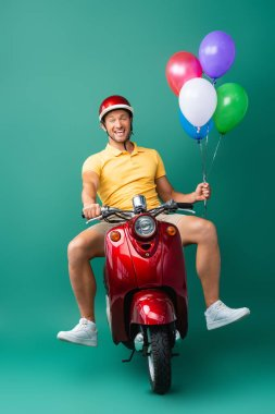 Excited delivery man in helmet riding scooter while holding balloons on blue stock vector