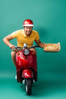 Cheerful delivery man in helmet riding scooter while holding tasty pizza in box on blue stock vector
