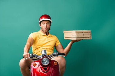 Surprised delivery man in helmet riding scooter while holding pizza boxes on blue stock vector