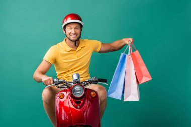 Happy delivery man in helmet riding scooter while holding shopping bags on blue stock vector