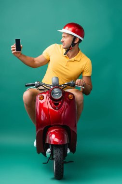 Delivery man in helmet riding scooter while holding smartphone with blank screen on blue stock vector