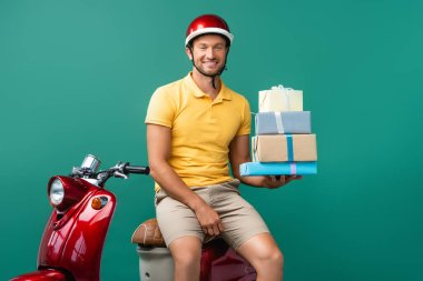 Happy delivery man in helmet holding wrapped presents near scooter on blue stock vector
