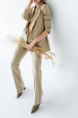 ořezaný pohled na mladý model v béžovém obleku při držení pšenice na bílém