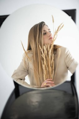 Reflection of young woman looking away while holding wheat with blurred chair on background stock vector