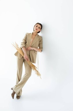 Full length of young woman in beige suit posing while holding wheat on white stock vector
