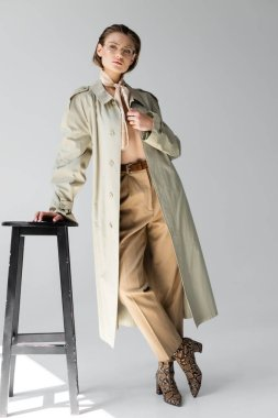Full length of young woman in glasses, trench coat and scarf leaning on stool while posing on grey stock vector