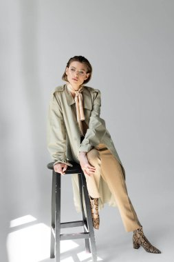 Full length of young woman in trench coat and scarf sitting on stool while posing on grey stock vector