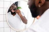 afro-americký muž kontroluje žvýkačku s bambusovým zubním kartáčkem