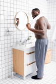 Fotografie full length of smiling afro-american man standing in bathroom with towel behind neck