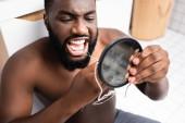 afro-americký muž sedí v malém zrcadle a používá zubní nit