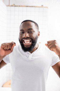 Portrait of afro-american man using dental floss stock vector
