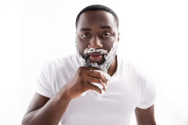 Afro-american man with shaving foam on face looking at camera stock vector