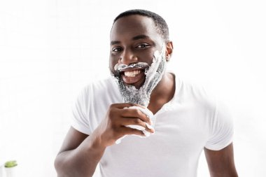 Smiling afro-american man with shaving foam on face looking at camera stock vector