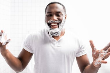 Laughing afro-american man with shaving foam on face looking at camera stock vector