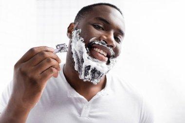 Portrait of happy afro-american man shaving beard with razor stock vector
