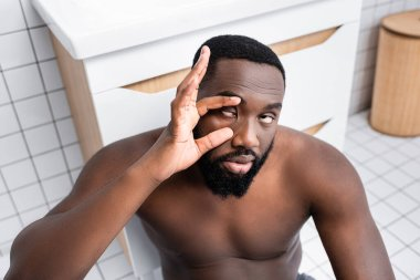 afro-american man trying not sleeping and holding eyelids