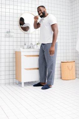 Full length of afro-american man brushing teeth in bathroom stock vector