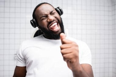 afro-american man with headphones singing in toothbrush