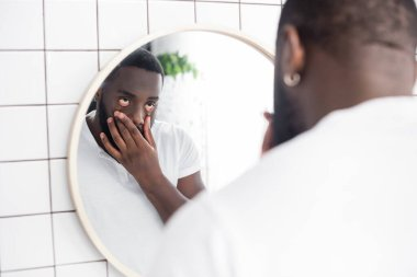 tired afro-american man pulling lower eyelids with fingers