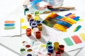 gouache barvy, štětce a abstraktní barevné tahy štětcem na papíře na bílém pozadí