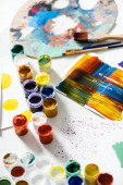 gouache paints, paintbrushes and abstract colorful brushstrokes on paper on white background