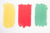 top view of abstract colorful green, yellow and red paint brushstrokes on white background