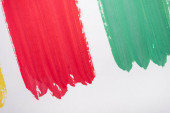 top view of abstract colorful green and red paint brushstrokes on white background