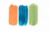 Draufsicht auf abstrakte bunte grüne, orangefarbene und blaue Pinselstriche auf weißem Hintergrund