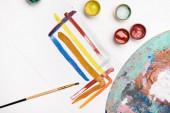 vrchní pohled na paletu s barvami Gouache a štětcem u papíru s tahy štětcem na bílém pozadí