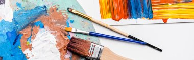 Top view of paintbrushes and abstract colorful brushstrokes on paper on white background, panoramic shot stock vector