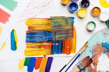 Top view of gouache paints, paintbrushes and abstract colorful brushstrokes on paper on white background stock vector