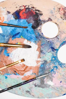 Top view of palette with paints and paintbrushes isolated on white stock vector