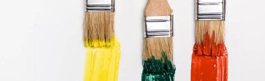 Top view of paintbrushes near colorful paint brushstrokes on white background, panoramic shot stock vector