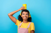 happy african american woman holding reusable mug above head on blue
