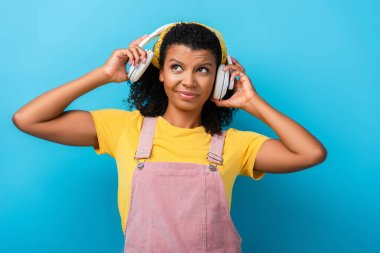confused african american woman in wireless headphones listening music on blue