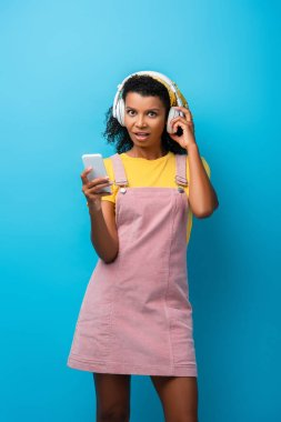 shocked african american woman in headphones listening music and using smartphone on blue