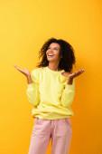 aufgeregte Afroamerikanerin blickt auf und gestikuliert auf gelb