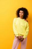displeased african american woman looking away on yellow