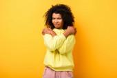 elégedetlen afro-amerikai nő átöleli magát sárga