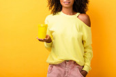 cropped view of african american woman holding reusable cup while standing with hand in pocket on yellow