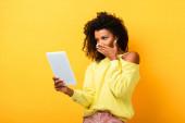 šokovaný afroameričanka drží digitální tablet na žluté