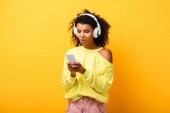 überrascht afrikanisch-amerikanische Frau in Kopfhörer mit Smartphone auf gelb