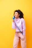 happy african american woman talking on blue retro phone on yellow