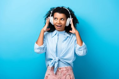 excited african american woman listening music in headphones on blue