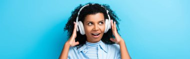 Excited african american woman listening music in headphones on blue, banner stock vector