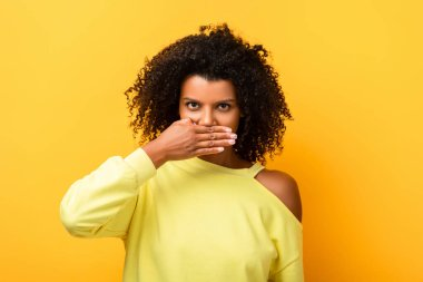 African american woman covering mouth and looking at camera on yellow stock vector